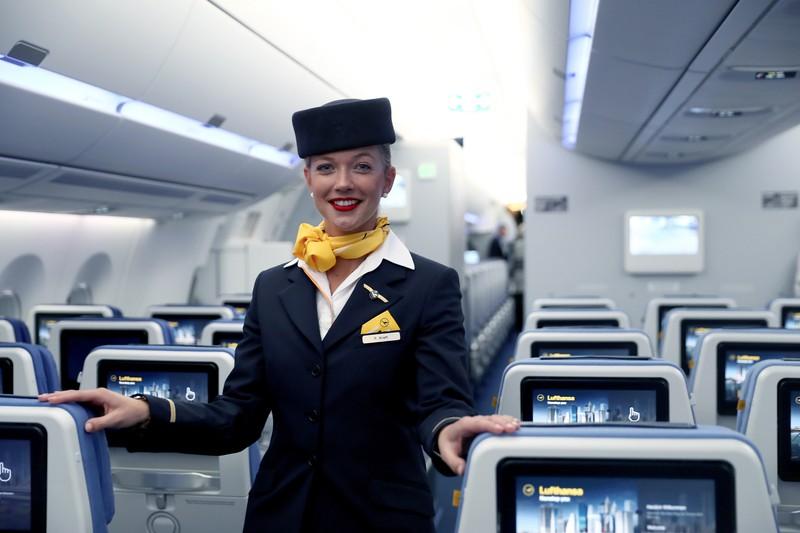 Eine Flugbegleiterin inspiziert ihre Fluggäste ganz genau.