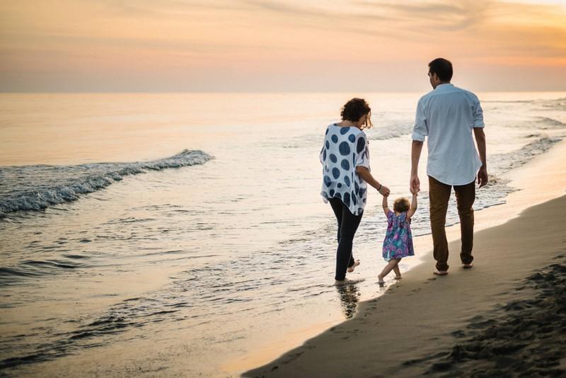 Eine Familie geht am Strand spazieren.