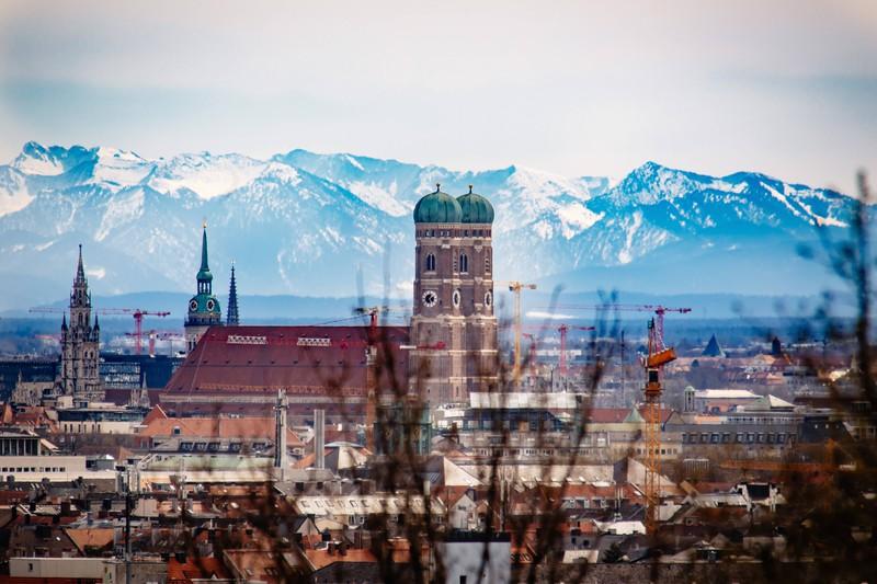 Zu sehen ist das Panorama der Stadt München vor den Alpen.