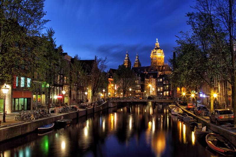 Zu sehen ist die Stadt Amsterdam bei Nacht.