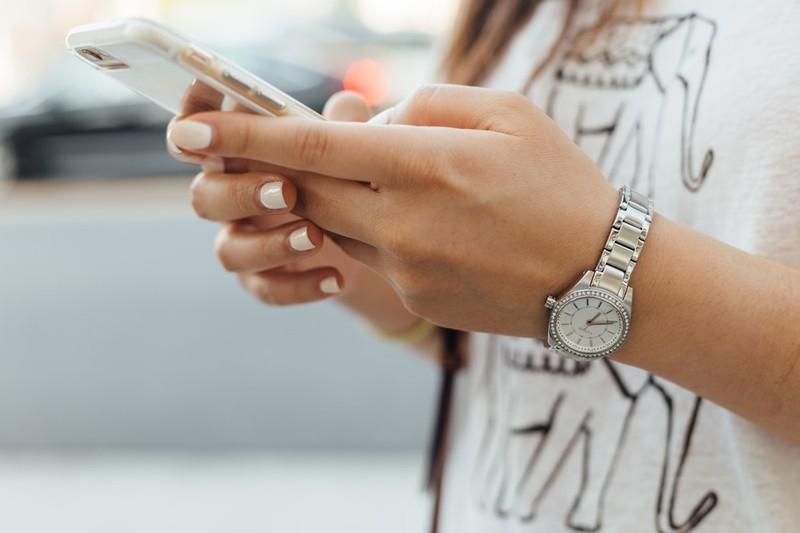 Dieses Bild zeigt eine Frau, die ein Smartphone in der Hand hält, wobei im Ausland teure Roaming-Gebühren anfallen können.