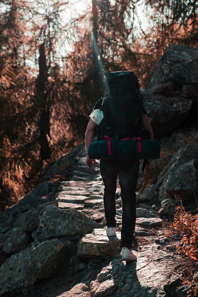 Dieser Mann trägt einen Rucksack auf Reisen, der sich einfach mit einem Packsystem ordnen lässt.