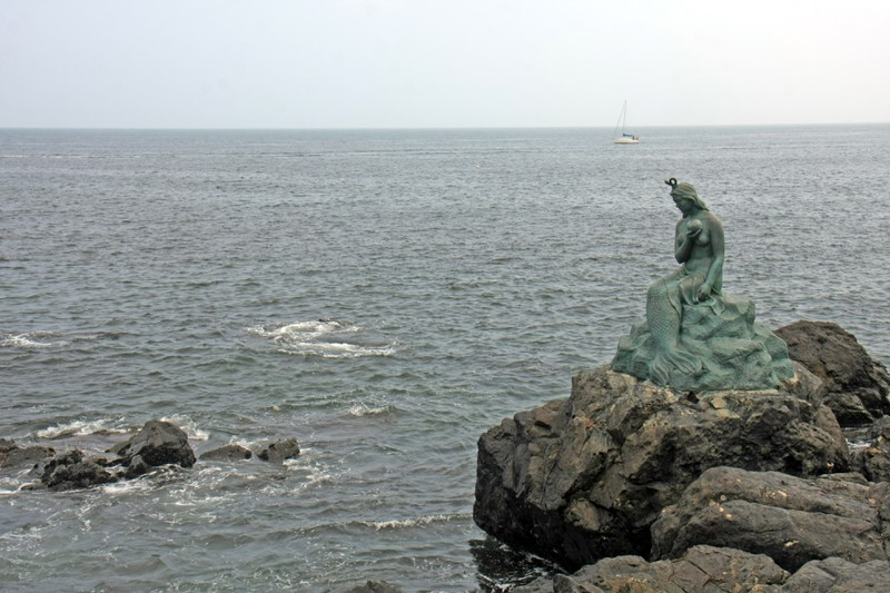 Auf den Klippen sitzt eine Bronzefigur