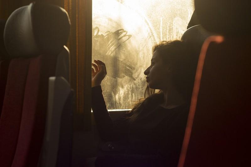 Frau, die am Fenster eines Reisebusses sitzt