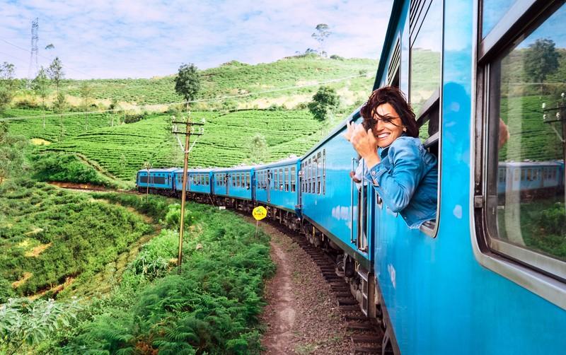 Frau fährt mit der Bahn bei offenem Fenster