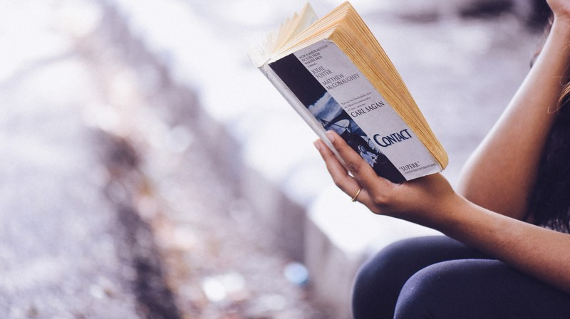 Frau, die eine digitale Auszeit nimmt und ein Buch liest
