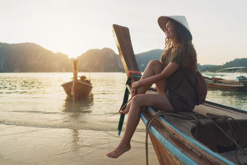 Frau schaut am Strand von Boot auf Wasser