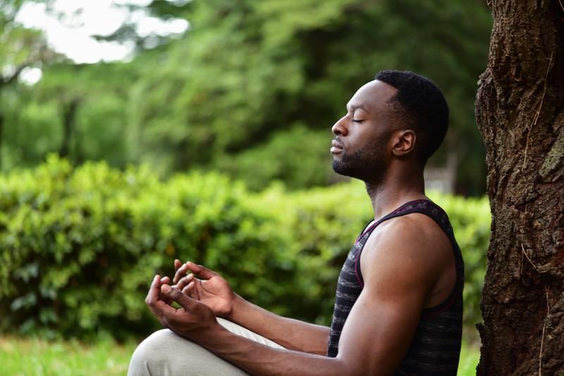 Mann meditiert im Freien