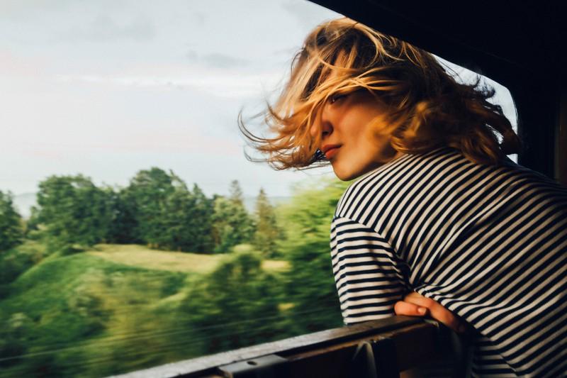 Frau fährt Zug mit offenem Fenster