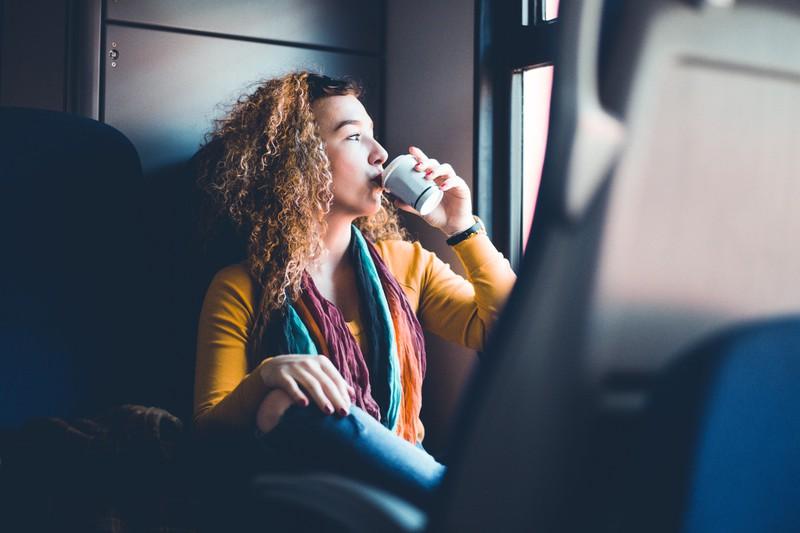 Frau trinkt Kaffee im Zug