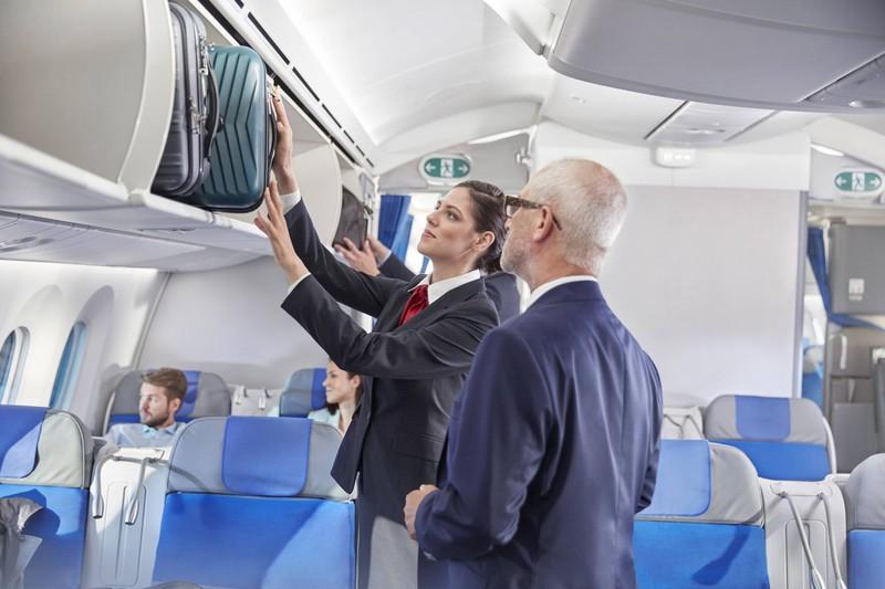 Man sieht eine Flugbegleiterin, die problemlos an die Gepäckfächer im Flugzeug gelangt