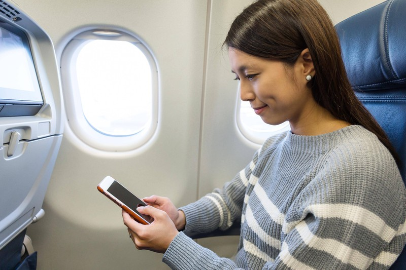Man sieht eine Frau, die ihr Handy in den Flugmodus stellt, damit dem Mythos zufolge das Flugzeug nicht abstürzen kann