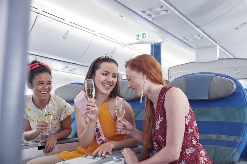 Man sieht Frauen, die Alkohol im Flugzeug trinken und denken, sie wären schneller betrunken. Der Mythos ist allerdings falsch
