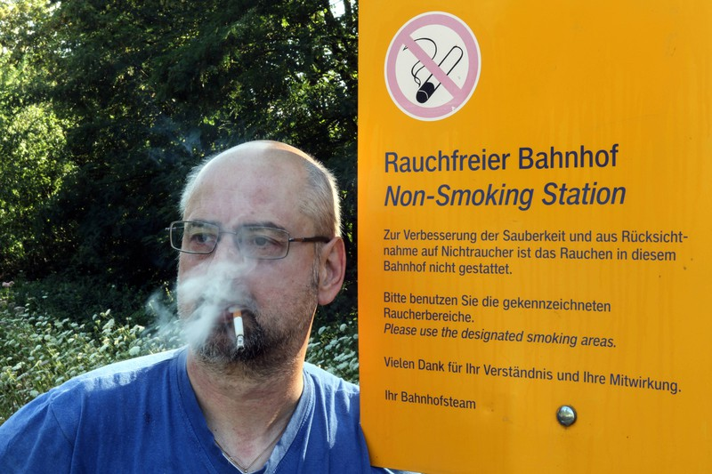 Ein Mann ignoriert das Rauchverbot an Bahnhöfen trotz eines entsprechenden Hinweisschildes: Starke Gerüche, wie einer Zigarette, können Reiseübelkeit verstärken.