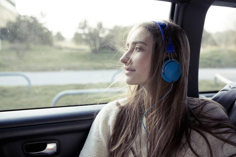 Eine Frau mit blauen Kopfhörern schaut bei der Fahrt aus dem Fenster, damit ihr nicht übel wird.