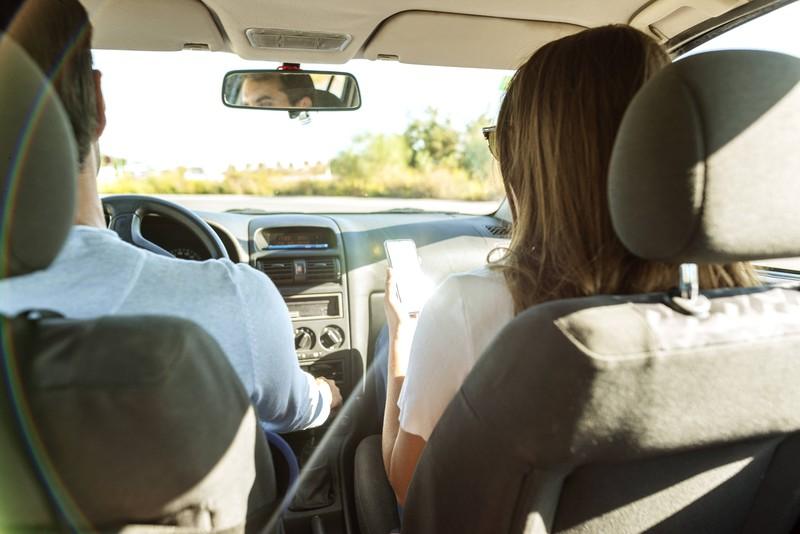 Eine Frau sitzt auf dem Beifahrersitz, weil ihr dort nicht so schnell schlecht wird