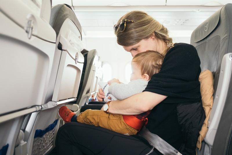 Eine Frau mit einem Baby. Die Frau darf am Flughafen aber Babynahrung in der Originalverpackung mit ins Flugzeug und ins Handgepäck nehmen