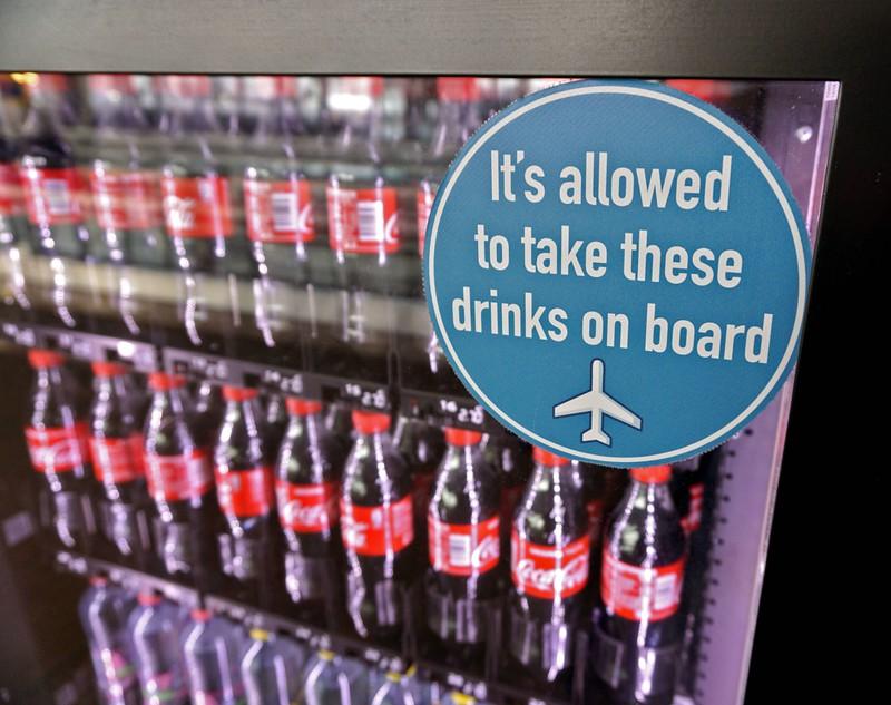 Es ist ein Snackautomat mit Getränken zu sehen, der zeigt, dass man jegliches Essen und Flüssigkeiten nach dem Sicherheits-Check ins Flugzeug mitnehmen darf