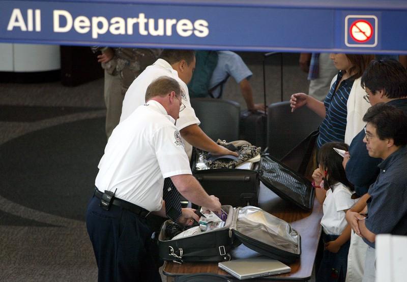 Männer durchsuchen Handgepäck am Flughafen am Security Check-in um vielleicht nach Flüssigkeiten und Essen zu kontrollieren