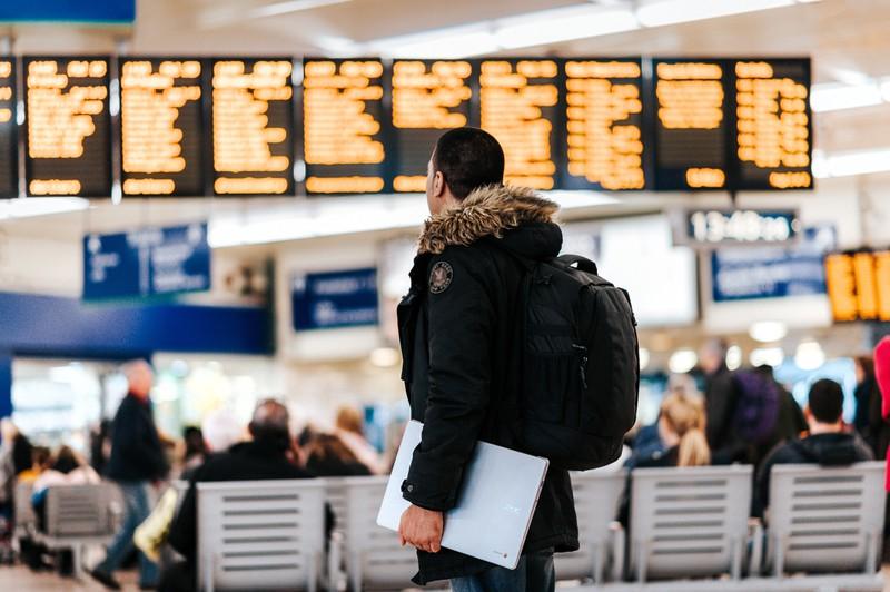 Ein Mann der gestresst am Flughafen nach seinem Flug sucht