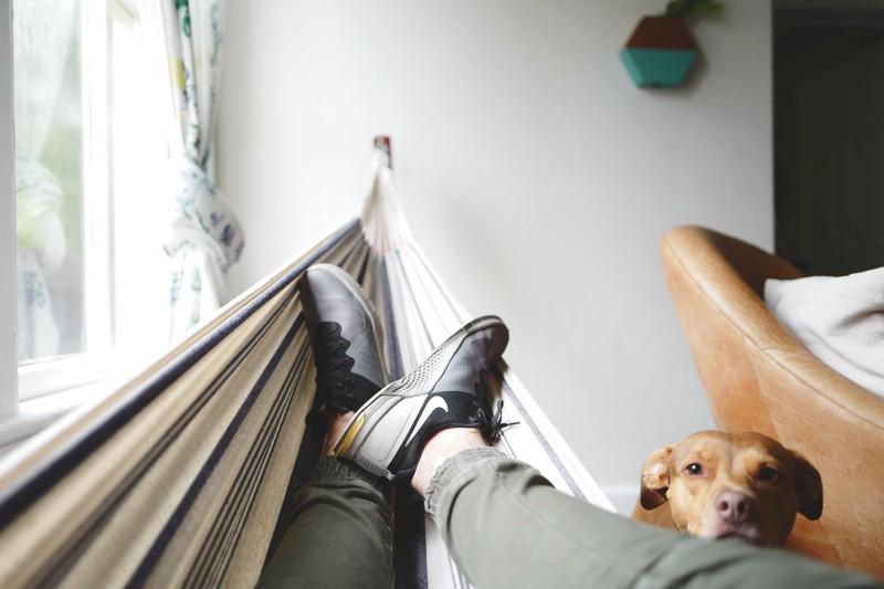Ein Mann, der Zuhause in einer Hängematte entspannt