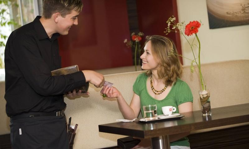 Eine Frau, die dem Kellner im Restaurant Trinkgeld gibt