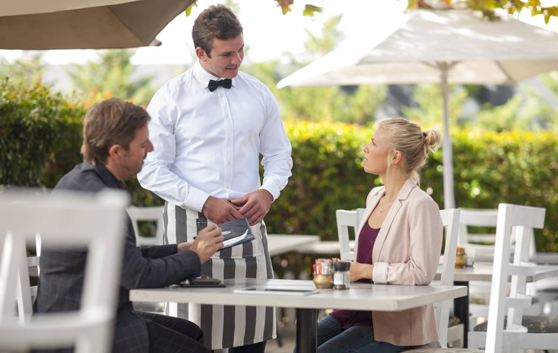 Kunden sitzen in einem sommerlichen Restaurant und werden vom Kellner bedient.