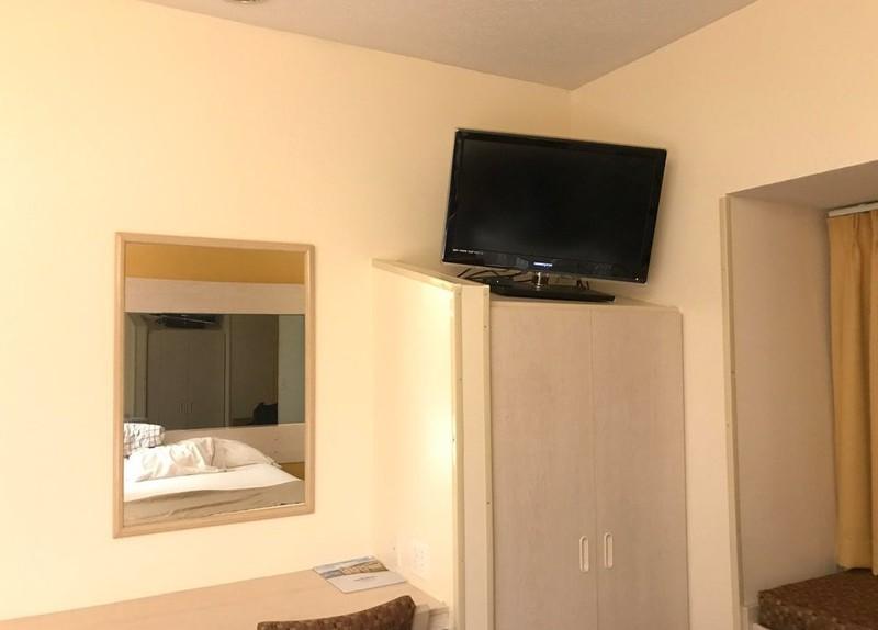 Ein Fernseher in einem Hotel, der sehr gefährlich auf einem Schrank steht