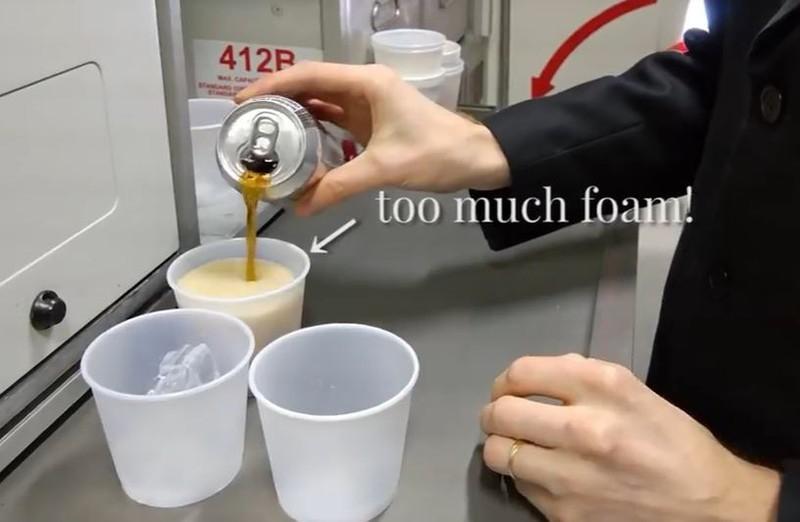 Ein Steward schenkt Cola in einen Becher im Flugzeug ein und die Cola schäumt überdurchschnittlich viel weswegen es länger als am Erdboden dauert das Getränk fertig zu füllen