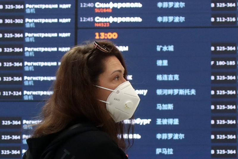 Urlaub in Zeiten von Corona: Eine Frau hält sich am Flughafen an die Maskenpflicht
