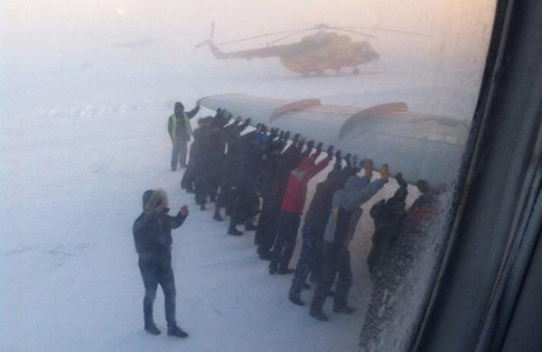 Ein verrücktes Foto, wie Leute in Russland ein Flugzeug anschieben