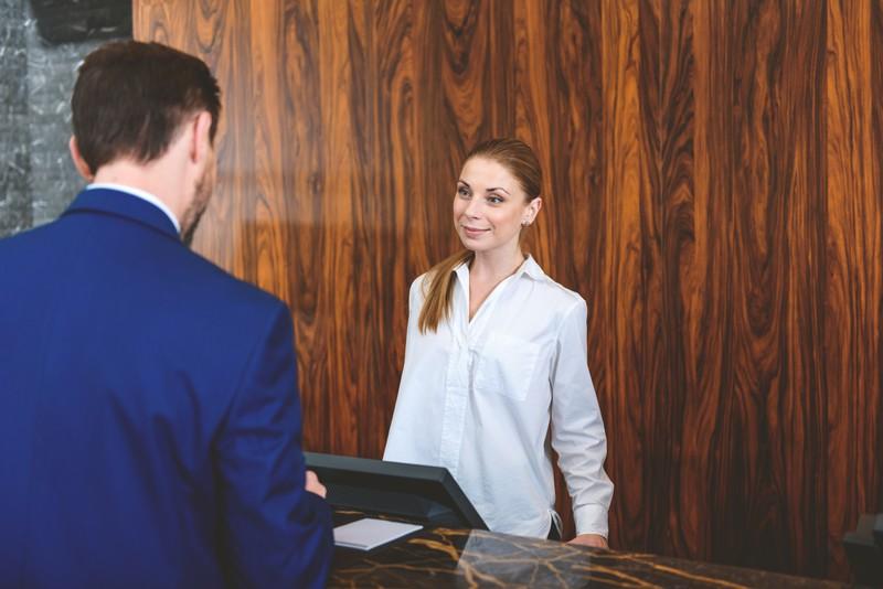 Ein Hotelangestellter und ein Hotelgast, die an der Rezeption des Hotels stehen