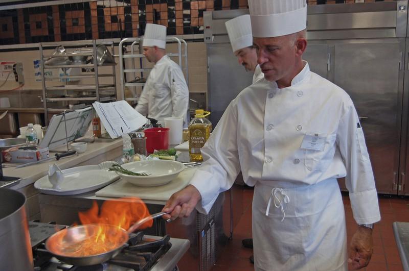 Ein Koch brennt etwas bei offenener Flamme in der Küche